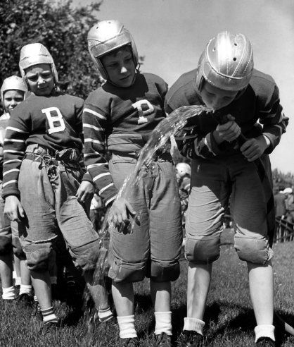 Thirsty young football players drink water from a watering hose in Denver, Colorado, in 1939. Alfred Eisenstaedt-Time and Life Pictures/Getty Images.
