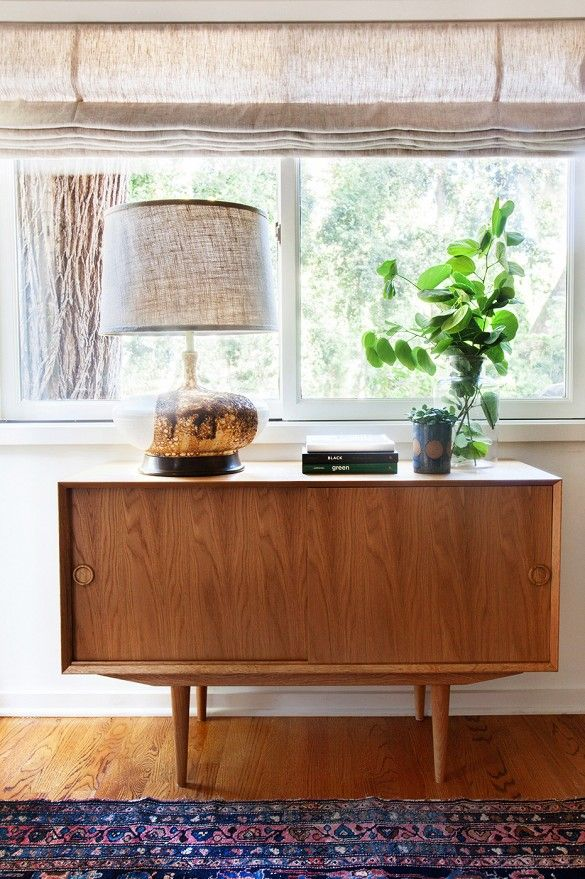 Wooden midcentury console with lamp, art books, and houseplant.