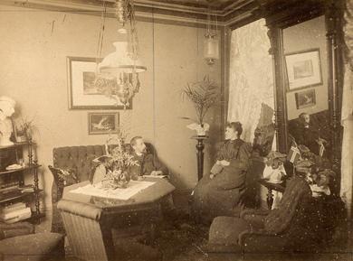 Tiden er omtrent midten av 1890 tallet, flere av de andre bildene i bergensalbumet etter fotograf Svanøe er datert 1894. Fotografiet viser et yngre par, sannsynligvis i familie, som er samlet i en koselig stue eller salong. Her er det kunst på veggene, en kunstferdig oppsats på bordet og potteplanter plassert rundt i rommet. En tidstypisk stue med parafinlysekrone som ga lys til rommet, og en mindre lampe i hjørnet som ga mer dempet lys. Det er en type lampe som kalles måneskinnslampe.