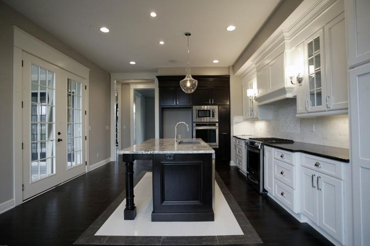 Sophisticated and elegant, this traditional gray kitchen features a spacious island with a granite countertop and prep sink. Crisp white cabinets pair with dark cabinetry and kitchen island for exquisite contrast.