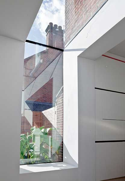 A glazed section joining extension and semi-detached house to allow the transition between brick and render