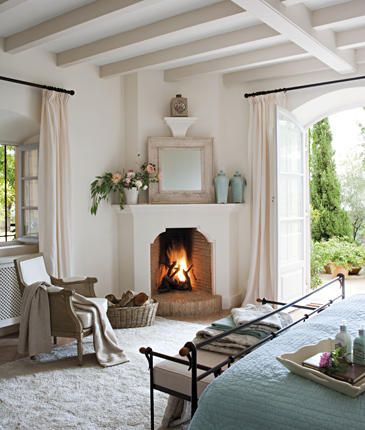 white bedroom with ceiling beams and fireplace