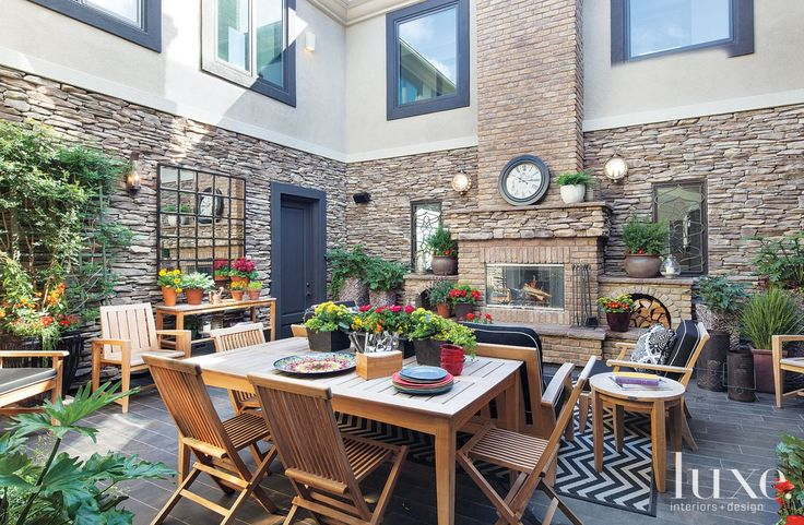 This outdoor courtyard appeal is defined by its stone veneer and warm outdoor furniture.