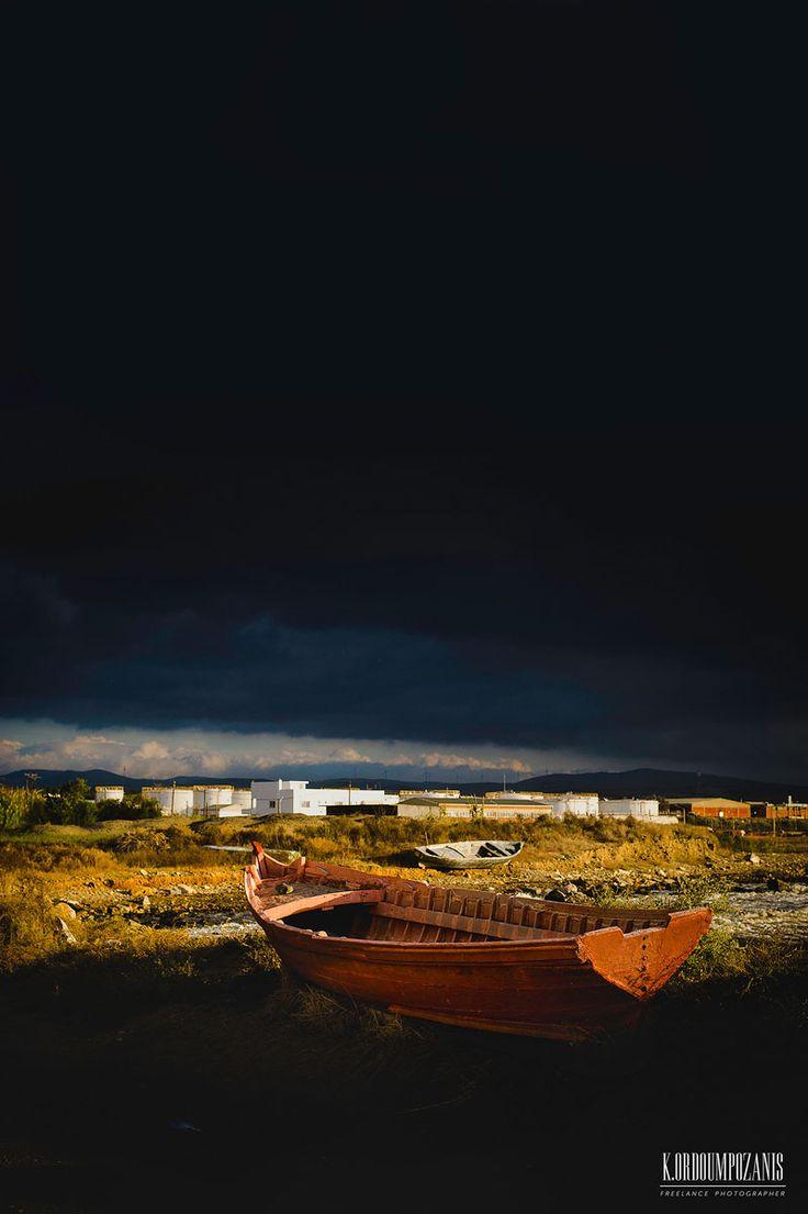 Landscape: A boat at sunrise in a sky full of dark clouds ©www.ko-photo.com