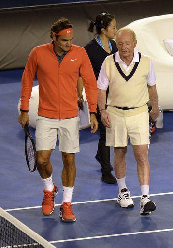 Roger Federer of Switzerland and Australian tennis great Rod Laver walk on the court for a warm-up hit during a gala charity exhibition match in a lead up to the Australian Open (AP)