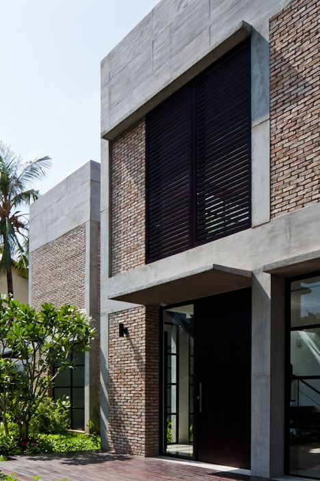 This house was stripped back to its concrete frame to create an open-plan villa featuring red brick walls, pivoting glass doors and leafy gardens.