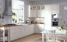 Cocina tradicional con armarios blancos, encimeras de madera, puertas de cristal y electrodomésticos integrados