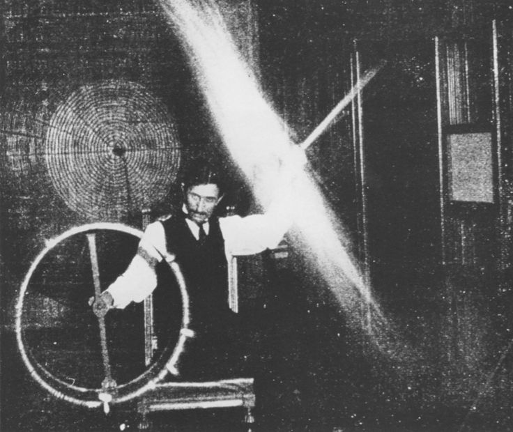May 5th, 1899 Tesla's body, in this experiment, is charged to a high potential by means of a coil responsive to the waves transmitted to it from a distant oscillator. A long glass tube waved in the hand is lighted to great brilliancy by the electrical charges conveyed to it through the body.