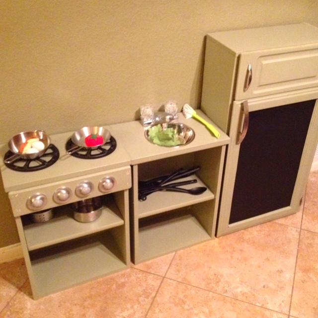 """I made this play kitchen for Tanner after being inspired on Pintrest. Each piece is made from a wooden drawer, the fridge is the drawer on its side. Most of the materials came from the Habitat Re-Store. The stove burners are car speaker covers we couldn't use, got the faucet on Craigslist for free!!!  Tanner loves being the """"Cooker Man"""" in his new kitchen. Now, get up and get crafty yourself!!"""