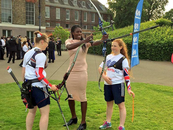 Kate made the rounds and was introduced to past and present athletes from the SportsAid program. It was a fascinating mix of black-tie and laid back. There was a basketball hoop set up as well as a number of other sports ranges, including archery. Below Christine Ohuruogu, an alumna of SportsAid and an Olympic athlete, tries her hand with the bow.