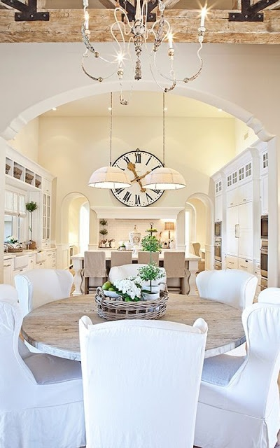This all white dining room is a dream and the open kitchen is an added bonus!