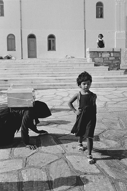 """An amazing photo by John Demos. Tinos island, Greece 1986. The woman on the left is a pilgrim, taking oil to the famous Tinos church as a """"token"""" of good faith for the Virgin Mary to perform a miracle; but notice the hand held by the little coquette on her waist on the right. Such poise! And such an antithesis. - Selected by www.oiamansion.com in Santorini."""