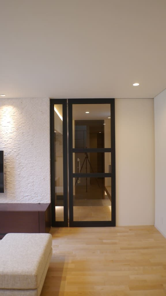 エントランスとリビングルームを結ぶ扉 モダンな 窓 ドア の 株式会社
