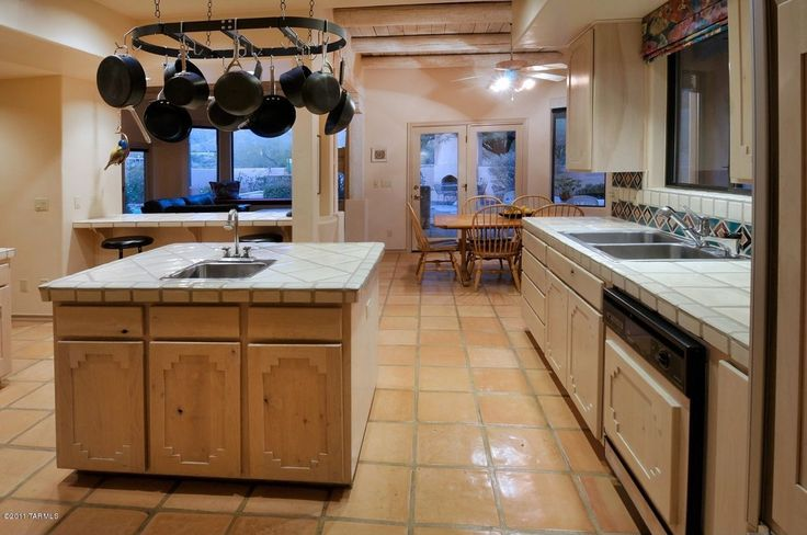 Southwestern Kitchen with Exposed beam, limestone tile floors, flush light, Kitchen island, European Cabinets, L-shaped