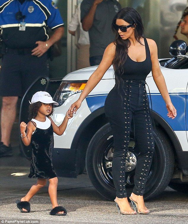 With mommy: North is always dressed up; here she had on a black velvet dress and furry slippers on September 18 in Florida