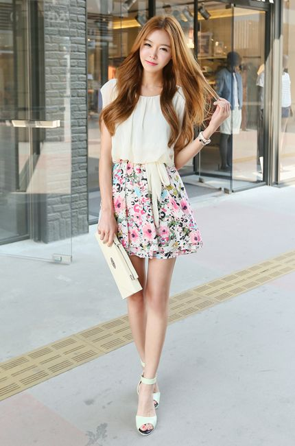 A floral skirt with a cream coloured blouse and accessories.