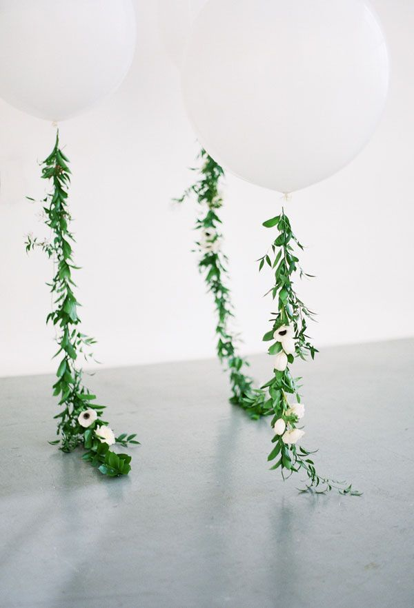 Large palm leaves hanging from the balloons rather than foliage garlands