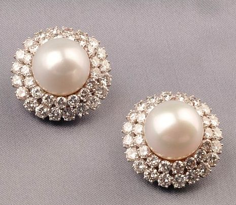 Platinum, South Sea Pearl and Diamond Earclips, Harry Winston, each set with a domed white pearl measuring approx. 15.00 and 15.25 mm, framed by full-cut diamonds, approx. total diamond wt. 12.00 cts., dia. 1 1/8 in., maker's mark.