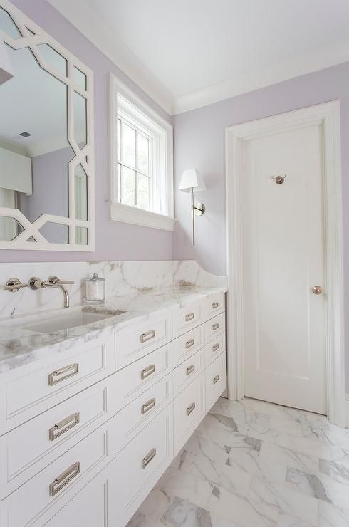 White and Lavender bathroom boasts a white trellis mirror, lining a lavender painted wall, placed over an extra-wide single washstand fitted with stacked drawers adorned with rectangular drop pulls topped with gray and white marble.