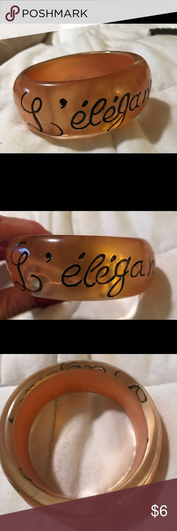 Gold Bangle Bracelet Ooh la la with this bracelet. Gold tone plastic resin material with scripted letters spelling L'elegance,  Worn only one time in great condition Jewelry Bracelets