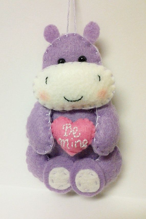 This sweet hippo ornament shows someone special how much they mean to you! He would be a lovely surprise as a Valentines Day gift.  He is made of purple felt and holds a little heart with a hand embroidered message that reads, Be Mine. Hang from a doorknob or anywhere, or set on a shelf or desk to keep a reminder of your loved one.  He is designed and handmade by me! He is about 4 1/2 inches tall. Find more cute felt critters here…