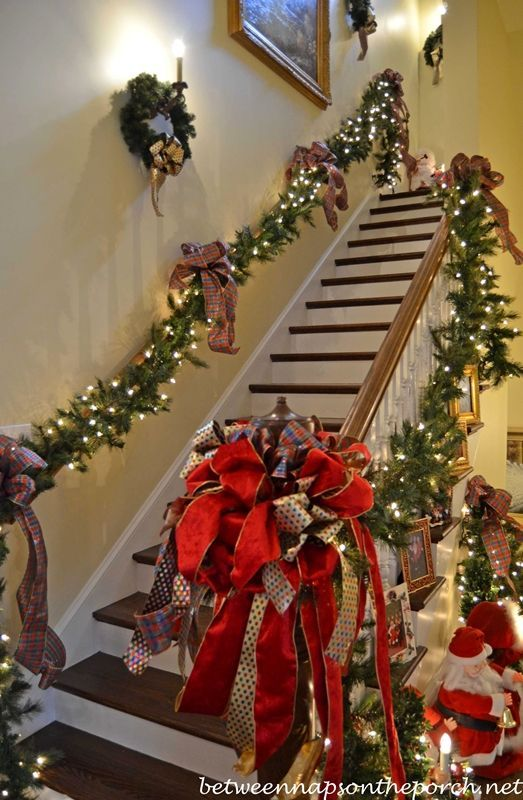 Stairway Decorated with Lit Garland and Ribbon for Christmas REMEMBER THIS BOW.