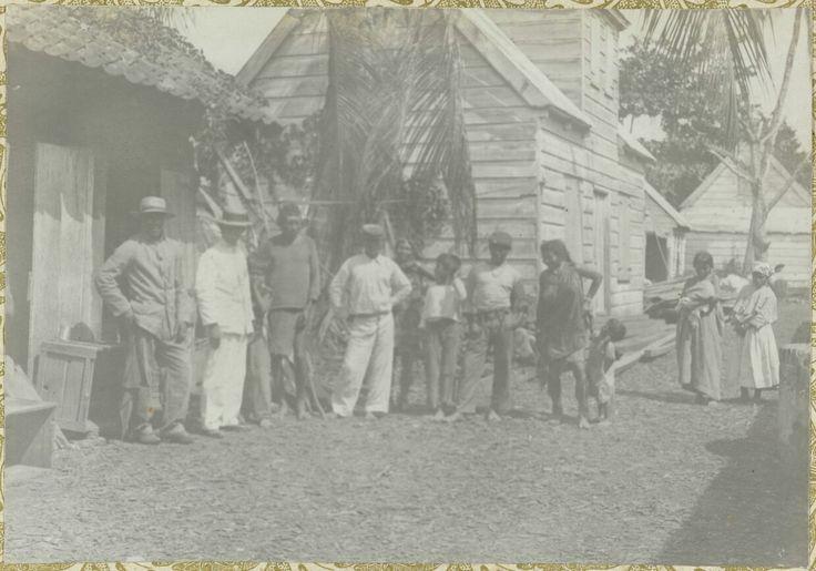 Omschrijving  Een groep van dorpelingen staande voor enkele huizen. Onderdeel van het fotoalbum Souvenir de Voyage (deel 1), over het leven van de familie Dooyer in en rond de plantage Ma Retraite in Suriname in de jaren 1906-1913.