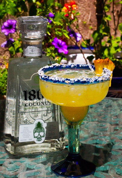 Coconut Margarita made from 1800 Coconut Tequila and fresh fruit juices, rimmed with toasted coconut.