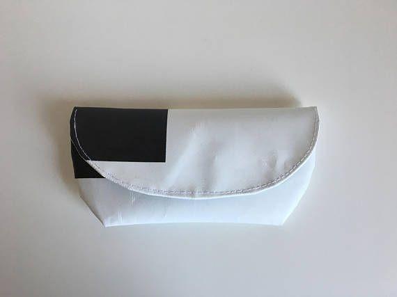 Etuit à lunette en bâche publicitaire recyclée, de fabrication artisanale. Etuit à lunette en bâche publicitaire recyclée de couleur blanc et noir Il se ferme à laide dun scratch. Lavable à la main, un coup déponge humide suffit. Taille: 18longueur / 9hauteur Les bâches sont