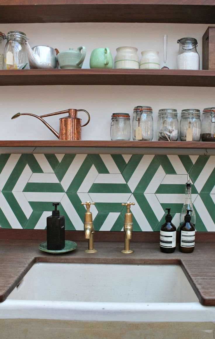Vintage style kitchen where Jamie Oliver cooks. Wood in earthy tone, brass fittings, emerald green patterned tiles.