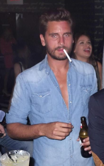 Scott Disick drinking alcohol and smoking a cigarette...