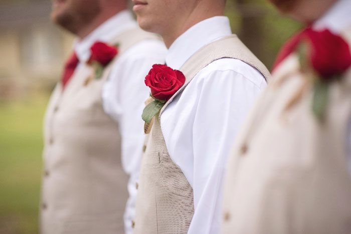 Groomsmen in tan vests, white shirts, red plaid ties, jeans, and cowboy boots with red rose boutonnieres.  | Outdoor vintage inspired wedding in Jacksonville, FL | ERINWIGGLE.COM