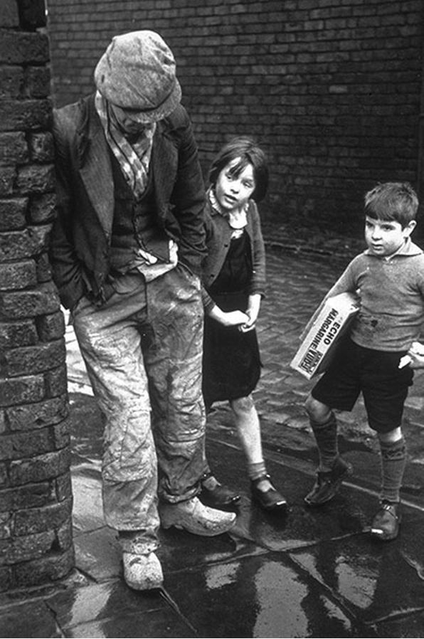 An unemployed man leaning against a wall with two children looking on, 1930s  photo by Kurt Hutton - Lancashire