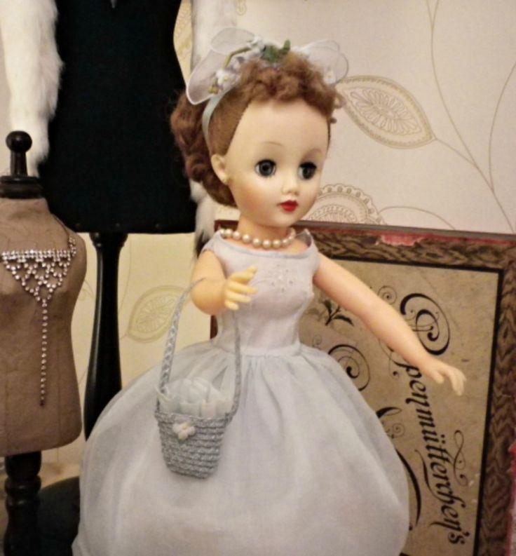Roberta, questo il suo nome, indossa un vestito in organza celste chiaro ricamato sul davanti con scollo a barca, spalla leggermente scivolata come usava negli anni '50, acconciatura con fiocco in raso e fiori d'epoca. Le parti dell'acconciatura in tulle sono degli anni '80, la borsa è in fettuccia di paglia inglese, l'unica cosa non vintage di tutto l'insieme. Vestito, acconciatura e borsa sono di mia creazione e realizzate manualmente. Collana in perle vintage inglese.