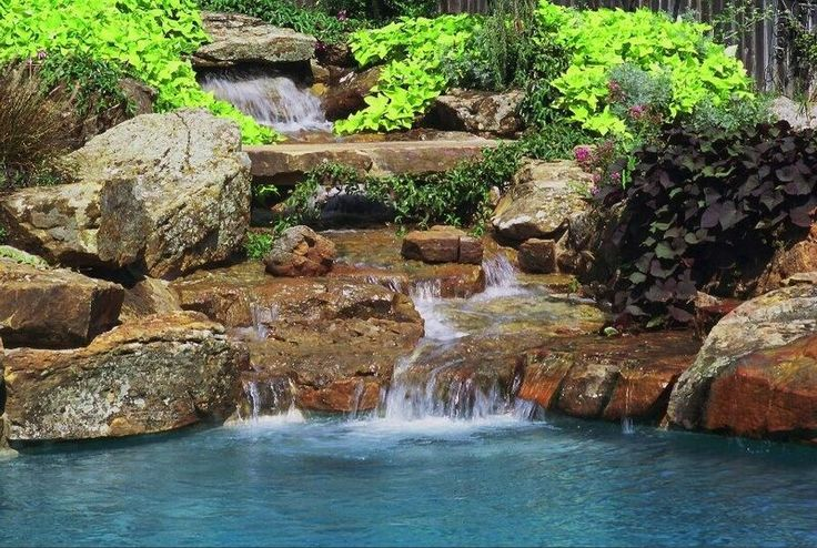 A natural stone waterfall cascades into the pool below. By Outdoor Signature in Argyle, TX.