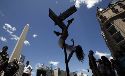 JUST HANGING AROUND--A pole dancer performs on a street sign to promote the Miss Pole Dance South America 2011 competition in Buenos Aires, Argentina, Thursday Nov. 10, 2011.  The pole dance competition is a one day competition on Friday.