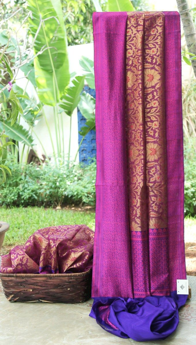 This purple Benares kora is packed with a floral pattern in gold zari with a hint of deep pink. The contrasting pallu and border are in berry blue intricately woven with hot pink thread making it a...