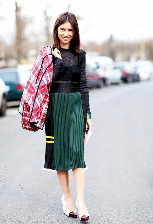 A bralette is worn over a sheer sweater, paired with a pleated knee-length skirt, plaid jacket, and two-tone wedges