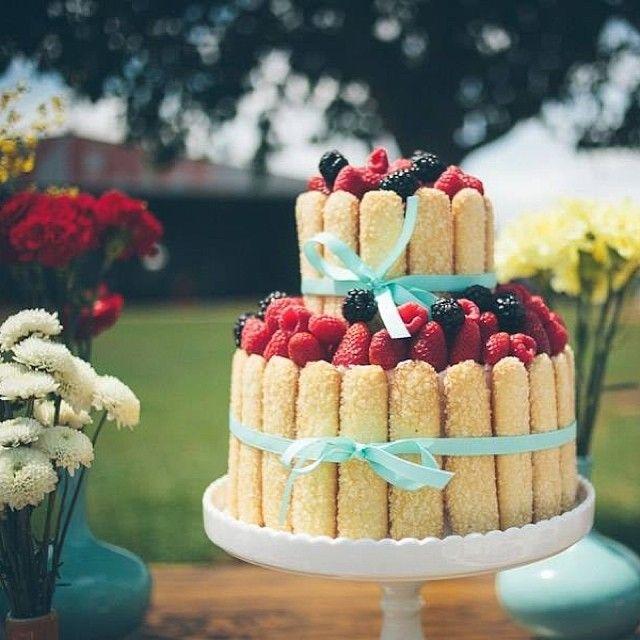 """A Charlotte típica é envolta em um """"cercadinho"""" de biscoitos champanhe, coberta de frutas vermelhas e amarrada com um laço de fita para finalizar. Tão delicado!"""