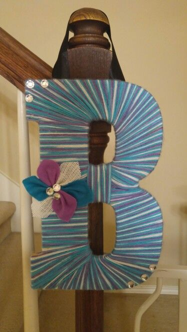 I wrapped wooden letter with tri-colored yarn using mod podge and hot glue. Also made flower from felt and white wired burlap. Dazzled with bling.