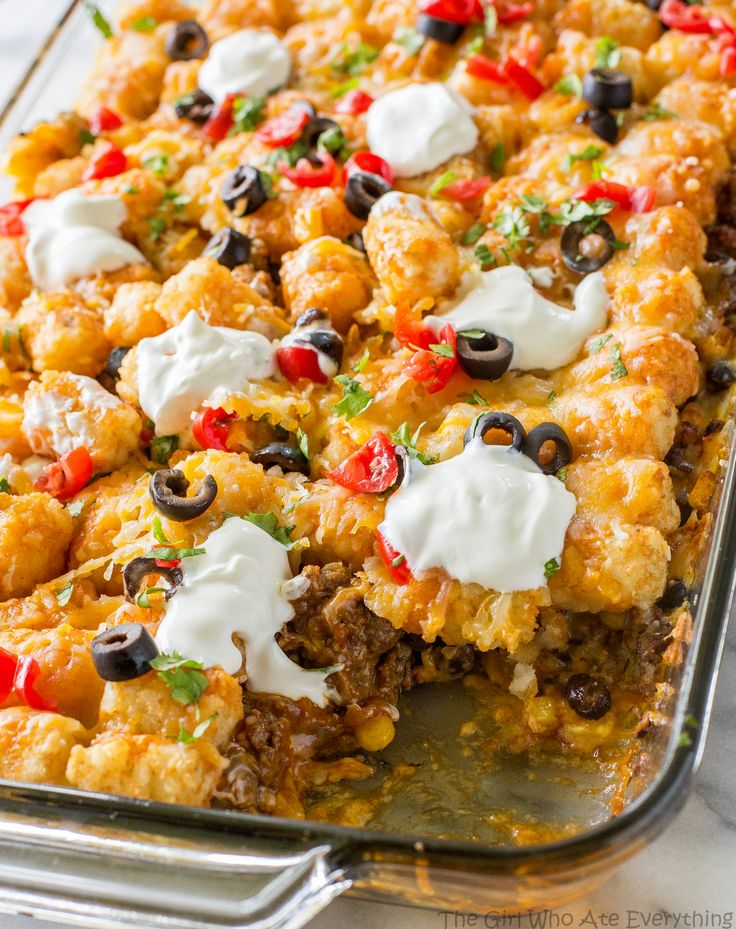 Tater Taco Casserole - A Mexican mixture of taco meat, beans, corn, and cheese topped with tater tots and enchilada sauce. the-girl-who-ate-everything.com