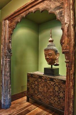 An antique Indian arch frames a Thai Buddha atop a 19th century Tibetan manuscript chest.