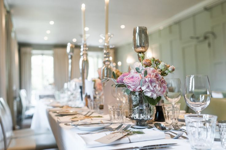 Elegantly set table for the wedding breakfast - Image by Ann-Kathrin Koch Photography - A wedding at Barnsley House with the bride in Suzanne Neville. A peony bouquet and white and blush colour theme. Mercury votive table decorations and white pom poms. Photography by Ann-Kathrin Koch.