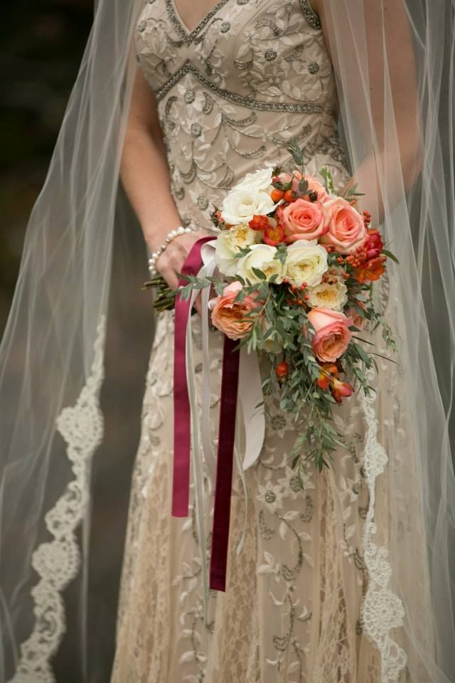 Maggie's wedding bouquet consists of light pink roses, white roses, spray roses, eucalyptus, berries, red freesia and other greenery. Cream and deep red ribbon is tied on the bouquet to create a unique element.: