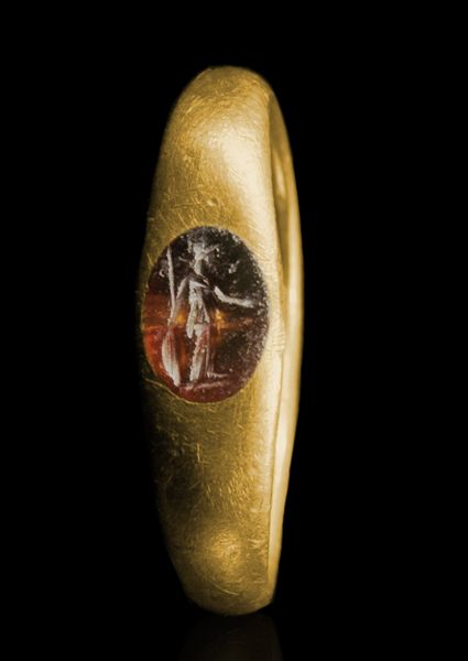 ROMAN GOLD FINGER RING WITH A CARNELIAN INTAGLIO OF ATHENA  Standing draped, looking to right, wearing a Corinthian helmet, and supporting a large shield and spear with her right hand and holding a phiale in her left.  2nd-3rd Century AD  Circum. 1 7/8 in. (4.7 cm.); wt. 4.1 gr.; Size 5  Ex D.T. collection, South Germany, since 1996.