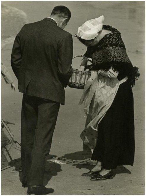Strand, een Scheveningse in dracht biedt iets te koop aan. 1967 N. de Lange #ZuidHolland #Scheveningen