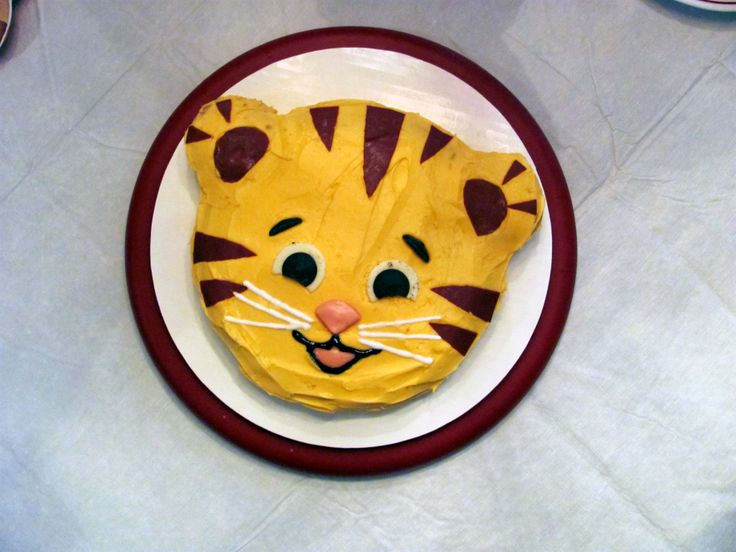 Daniel Tiger cake I made. Yellow cake with vanilla frosting died orange with gel icing. Pink Starburst nose & mouth. Filling of Oreos for whites of eyes. Chocolate melts for eyebrows & pupils. Brown sugar sheet for stripes & ears.