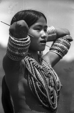 India | Konyak Naga girl posing for a photograph. she is wearing a colourful porcupine needle/quill through her ear. Wakching, Nagaland, Mon District. 1937. | ©SOAS, Nicholas Haimendorf