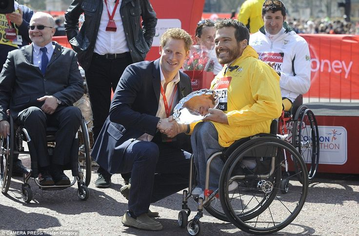 Prince Harry presents Kurt Fearnley, winner of the Mens Wheelchair race, with his trophy