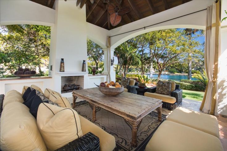 A+rustic+elegance+defines+a+host+of+outdoor+patios+and+covered+terraces+that+flank+the+home,+including+this+comfortable+lounge+with+an+outdoor+fireplace.+Open-air+living+is+a+must+in+this+waterfront+hacienda.